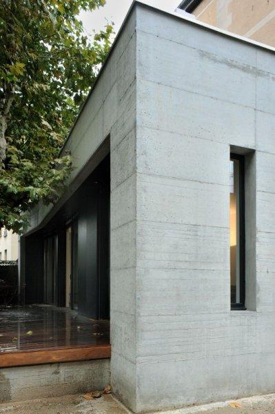 Mur béton, terrasse bois, larges baies vitrées